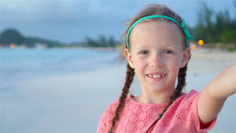 Happy little girl taking selfie at tropical beach on exotic island during summer Footage