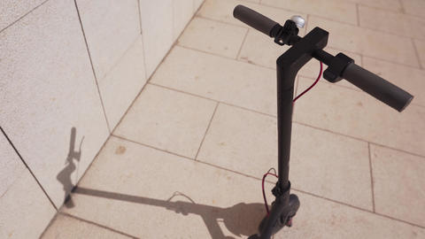 Detail of electric scooter. Smart scooter casts a shadow on a sunny day outside Footage