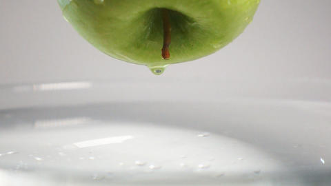 Drop of water falling down from apple into water Live Action