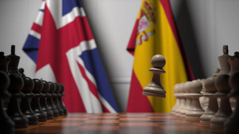 Chess game against flags of Great Britain and Spain. Political competition Live Action