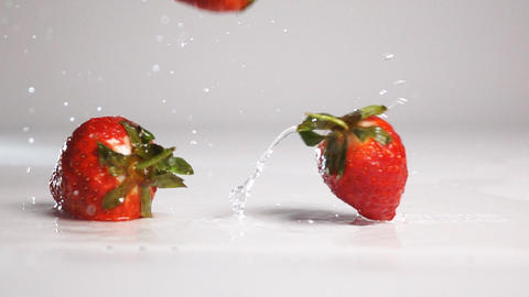 Strawberries fall on white wet surface Footage