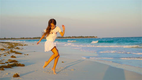 Active little girl at beach having a lot of fun. Sporty kid dancing on the Footage