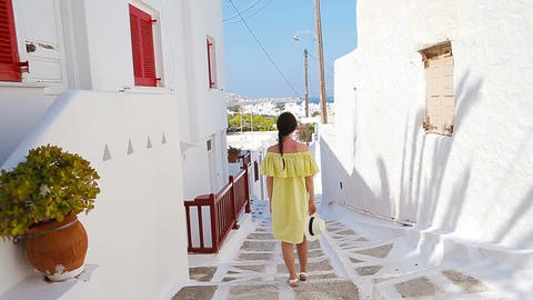 Beautiful woman outdoors in old streets an Mykonos. Girl at street of typical Live Action
