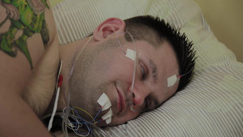 The patient is a man lying on a couch with a device for examination on the body Footage