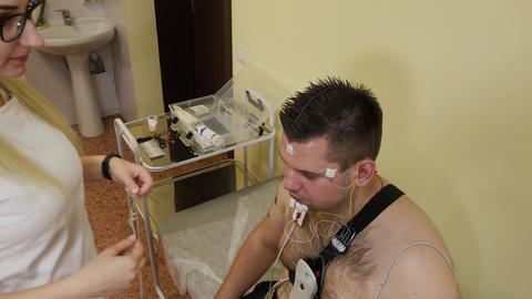 To a patient in a clinic, a male nurse puts a device on his body to study body Live Action