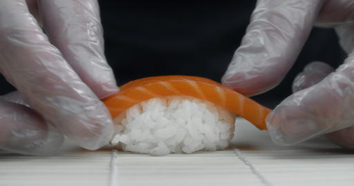 Chef puts salmon slice to the rice, making the nigiri in slow motion, cooking Footage