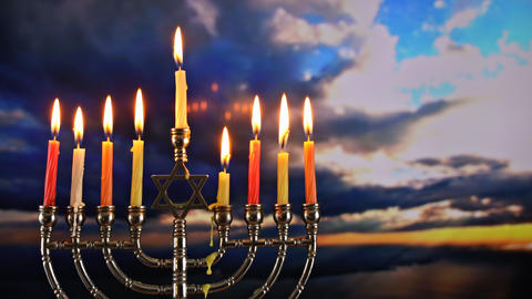 Hanukkah menorah with candles, sunset sky background Live Action