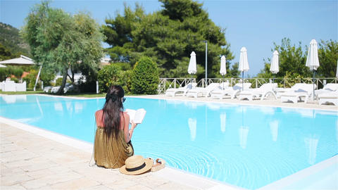 Woman relaxing by the pool in a luxury hotel resort enjoying perfect beach Footage
