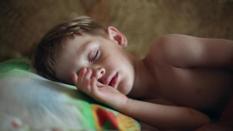 Little boy sleeping, he wakes up and stretches Footage