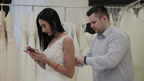 Handsome man fastens a wedding dress to his woman in a wedding salon Live Action