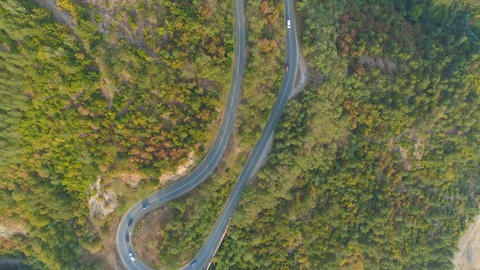 Top view of curvi mountain road with many cars driving. People on road trip Live Action