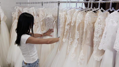 Beautiful girl chooses a wedding dress in a wedding salon, a man hides in Live Action