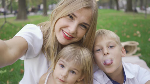 Pretty caucasian woman and her two kids looking at camera smiling. Woman taking Footage