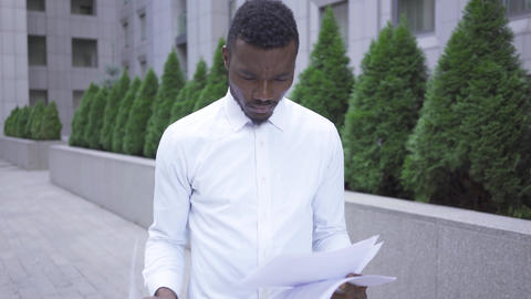 Troubled young African American man in white shirt looking through papers Live Action