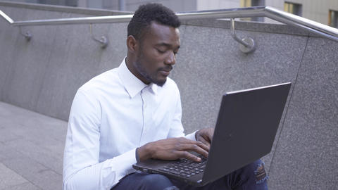 Positive African American man in white shirt typing on laptop sitting on the Footage