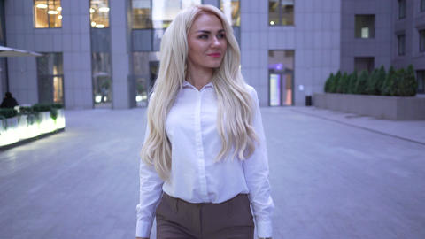 Blond smiling caucasian businesswoman walking on the city street and smiling Live Action