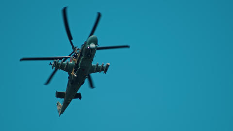 An army green camouflage coloring helicopter flying in the sky - gaining speed Footage
