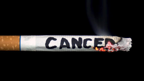 "A cigarette smolders with the word ""Cancer"". Cigarette on a black isolated Live Action"