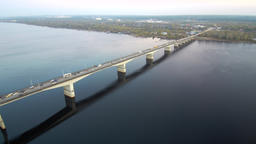 Aerial view of a long bridge over a wide river, active traffic on the bridge.the Footage