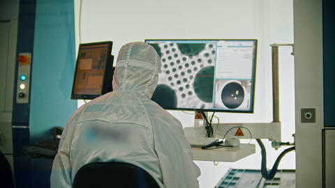 A man worker in protective white protective suit sitting by the monitor - cosmos Footage