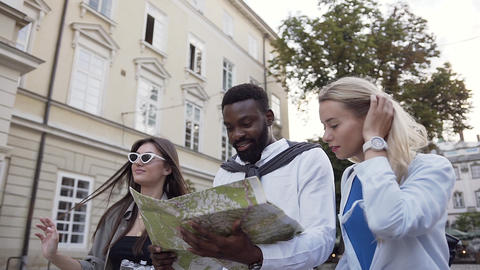 Likable happy young people walking on the street with beautiful architecture and Live Action