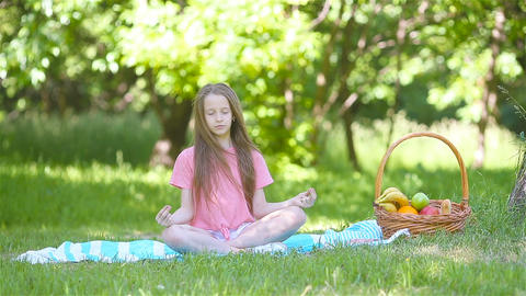 Little girl in yoga position in the park Footage