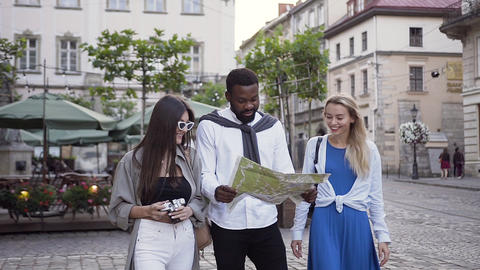 Carefree happy 30s people looking at city map and walking on the beautiful city Footage