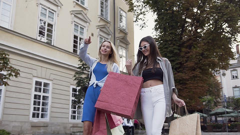 Attractive carefree women with various shop bags walking down the urban street Live Action