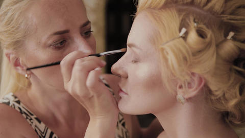 Professional make-up artist applies make-up photo of model to woman Live Action