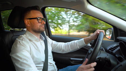 Bearded man in glasses and white shirt driving a car in sunny weather. Side view Live Action