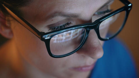 Woman in glasses looking on the monitor and surfing Internet. The monitor screen Footage