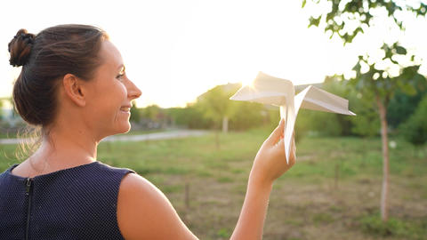 Woman launches paper airplane against sunset background. Concept of dreaming Live Action