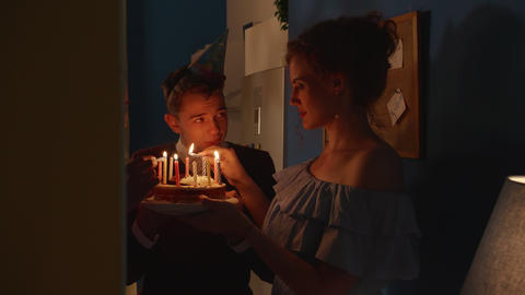 People stand with a cake in the dark Live Action