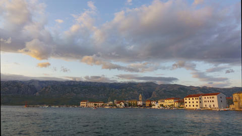 Day to night time lapse of small coastal town and harbor, mountains and rolling Live Action