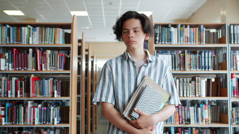 Portrait of serious teenage boy walking in school library with books alone Footage