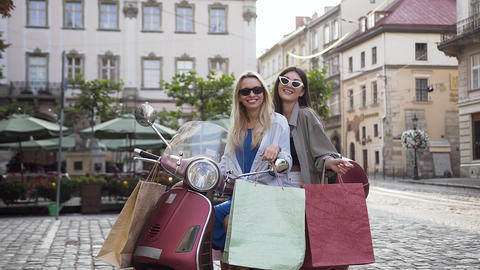 Lovely cheerful female friends in trendy sunglasses sitting on the scooter with Footage
