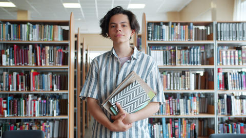 Cheerful teenager walking in college library holding books looking at camera Footage
