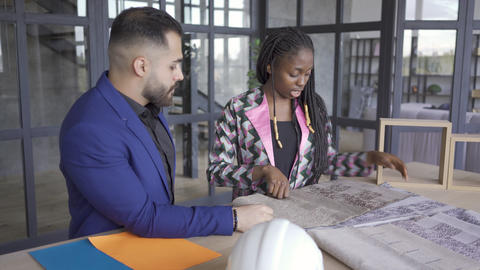 Beautiful multicultural couple choosing upholstery and style of furniture Footage