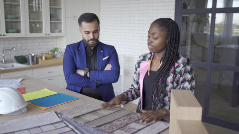 Satisfied multicultural couple talking while choosing upholstery and style of Footage