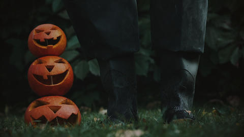 Scary story with jack-o-lanterns and unrecognizable man in rubber boots Footage