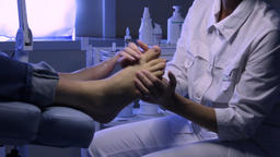 The podologist massages the patient's feet.Podology Live Action