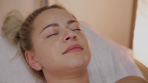 Beautiful young woman in bathrobe lying and waiting facial care procedure at Live Action