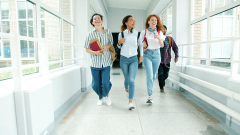 Dolly shot of happy youth running in college hallway holding books laughing Live Action