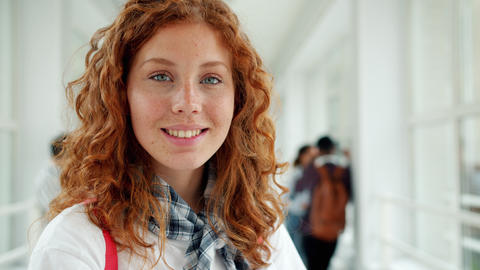 Portrait of pretty young lady student smiling looking at camera in college hall Footage