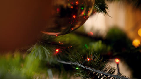 4k video of camera slowly moving between Christmas tree decorated with colorful Footage