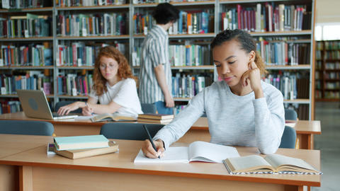 Group of students working in library reading books writing studying indoors Live Action
