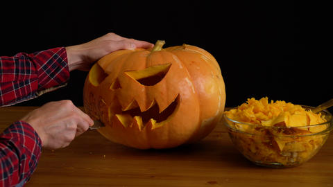 Men Carve Jack O' Lantern pumpkin for Halloween Celebration Footage