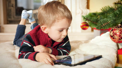 4k video of smiling little boy browsing internet and playing video games on Footage