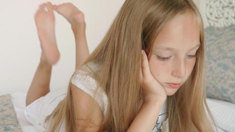Cute teenager girl lying on white bed looking smartphone. Blonde girl teenager Footage