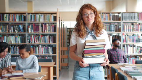 Serious redhead lady walking in library with bunch of books looking around Footage
